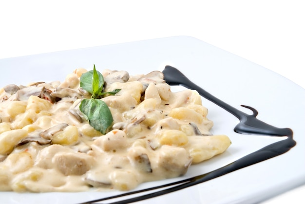 Meat under white sauce on the plate