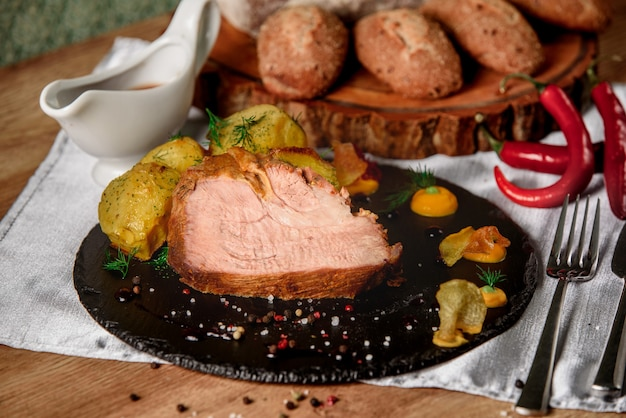 Meat with baked potatoes with dill, sauce and mustard on a black slate dish next to chili peppers and buns and bread on a wooden board.