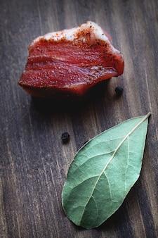 Мясо с лавровым листом на деревянной поверхности.