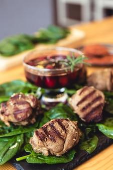 Мясо со свежей зеленью и вишневым соусом, готово к употреблению.