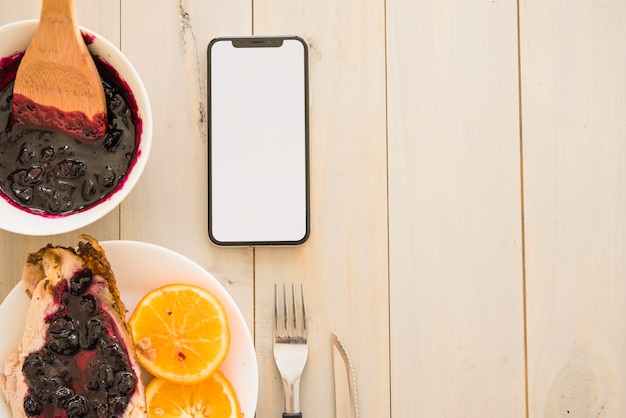 Meat with jam near oranges and smartphone