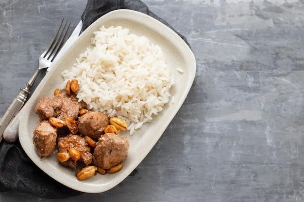 세라믹 테이블에 흰 접시에 견과류와 삶은 쌀과 고기