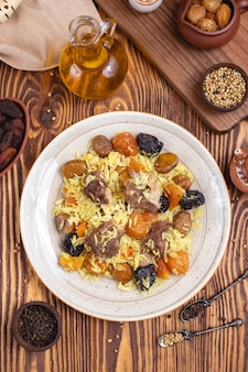 Meat with rice dry fruits prunes chestnuts spices oil top view