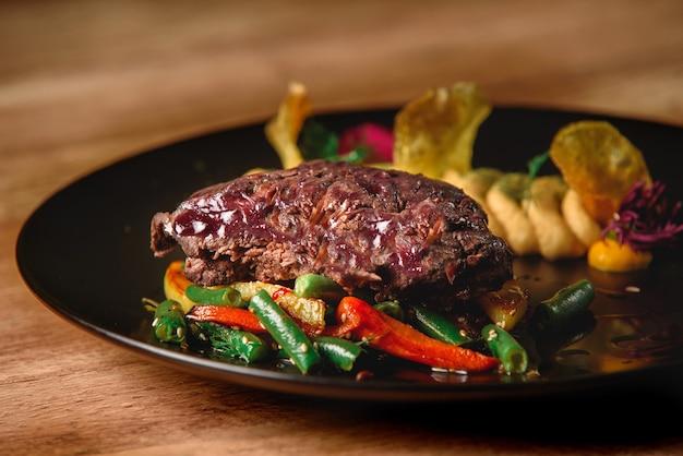 야채와 고기와 검정 잉크 판에 장식. 야채와 쇠고기. 맛있는 레스토랑 요리.