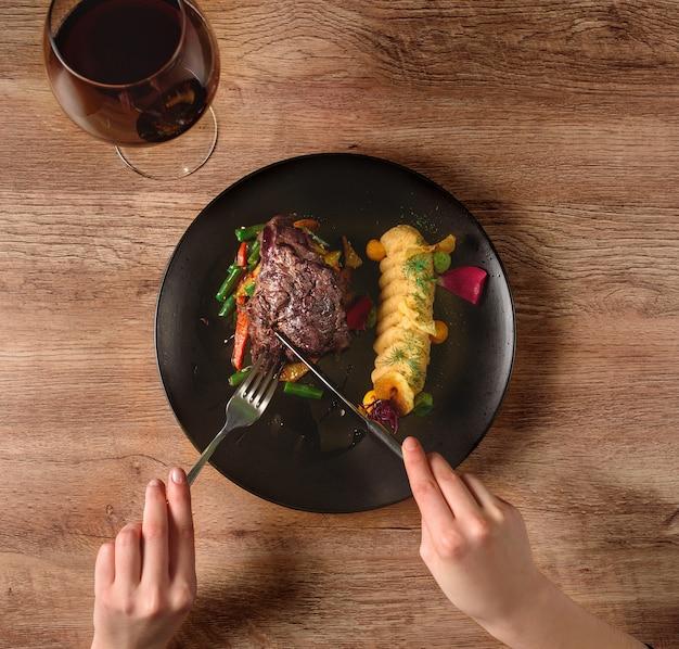 Мясо с овощами и гарниром на черной тарелке. говядина с овощами. вкусное ресторанное блюдо.