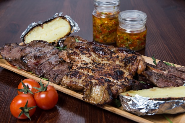 Meat with vegetables on a wooden plate