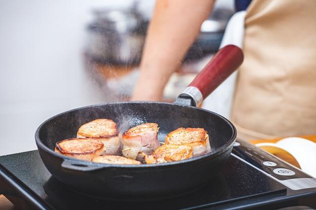 Мясо в беконе, обжаренное в чугунной сковороде на плите, на заднем плане - шеф-повар в фартуке. кухня, приготовление пищи, кулинария. ресторан, кафе, забегаловка. кулинарные курсы.