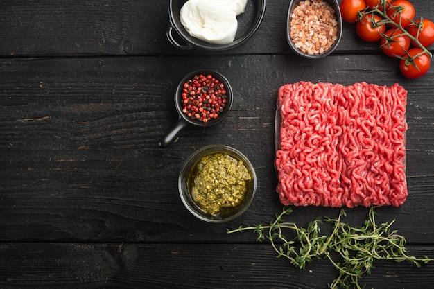 미트볼 재료 송아지 고기 또는 검은 나무 테이블에 향신료와 허브 세트가있는 혼합 수제 다진 고기, 평면도 평면 누워