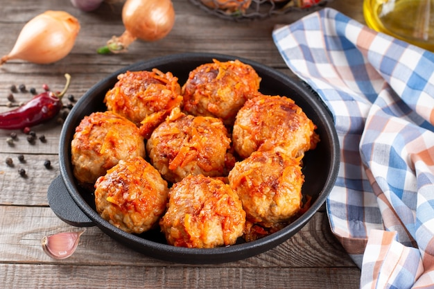 Meatballs from beef and pork with vegetables in a frying pan on a wooden table