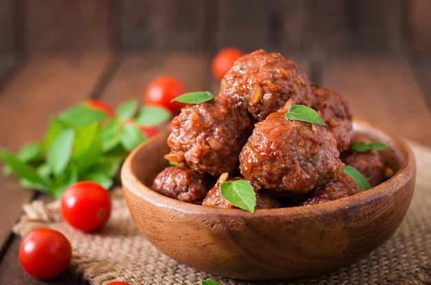 木製ボウルに甘酸っぱいトマトソースとバジルのミートボール