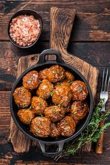 Тефтели в томатном соусе из говядины и свинины с тимьяном на деревенской сковороде. темный фон. вид сверху.