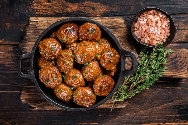 소박한 냄비에 백리향과 쇠고기와 돼지 고기에서 토마토 소스의 미트볼. 어두운 배경입니다. 평면도.