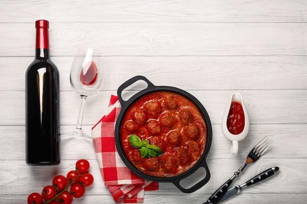 Фрикадельки в томатном соусе на сковороде с бутылкой вина, двумя стаканами, ножом и вилкой на белой деревянной доске