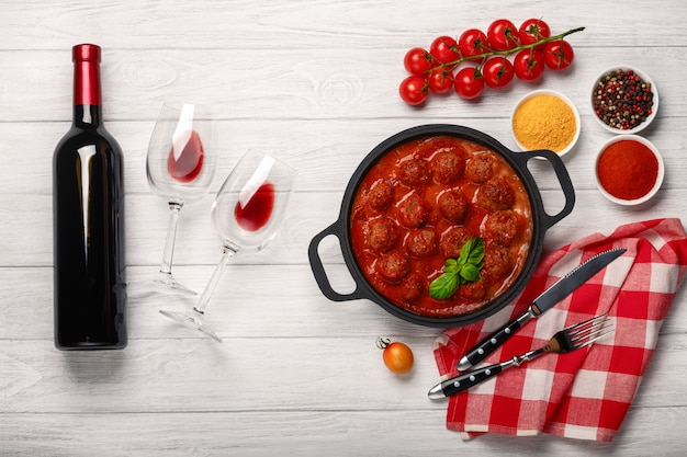 Фрикадельки в томатном соусе на сковороде с вишней, помидорами, бутылкой вина и двумя стаканами
