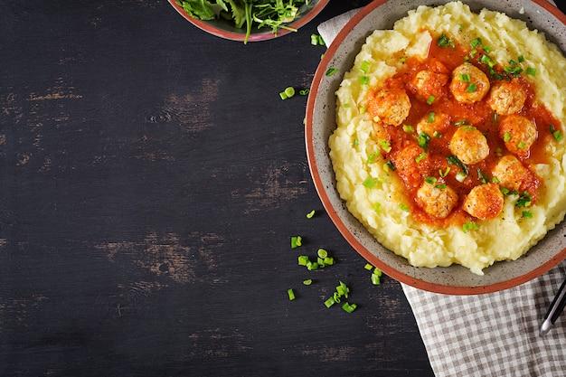 Фрикадельки в томатном соусе с картофельным пюре в миске.