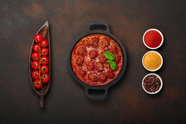 Фрикадельки в томатном соусе со специями, помидорами черри, паприкой, куркумой и базиликом на сковороде на ржаво-коричневом фоне