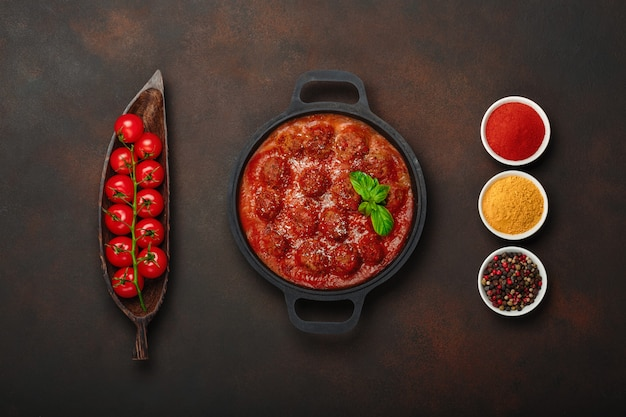Фрикадельки в томатном соусе со специями, помидорами черри, паприкой, куркумой и базиликом на сковороде