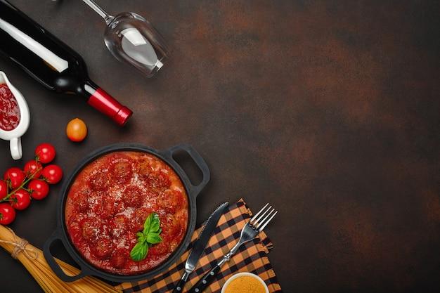 Фрикадельки в томатном соусе со специями, помидорами черри, пастой и базиликом на сковороде с бутылкой вина и рюмкой на ржаво-коричневом фоне