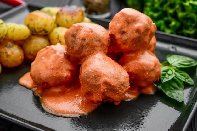 Тефтели в томате, с отварным картофелем на черной тарелке, на черной поверхности