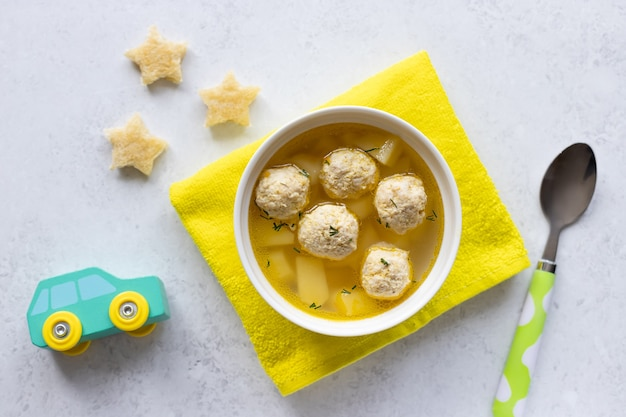 Meatballs soup for children with croutons with car toy, a spoon and yellow tablecloth