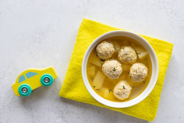 Meatballs soup for children with croutons with car toy and yellow tablecloth