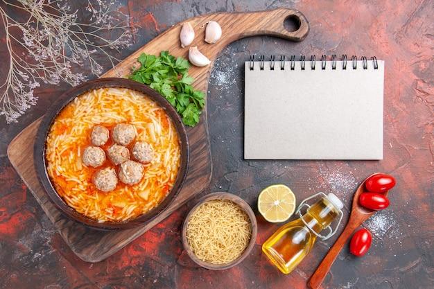 Zuppa di polpette con noodles a bordo di pasta cruda, verdure al limone e taccuino su sfondo scuro immagine stock