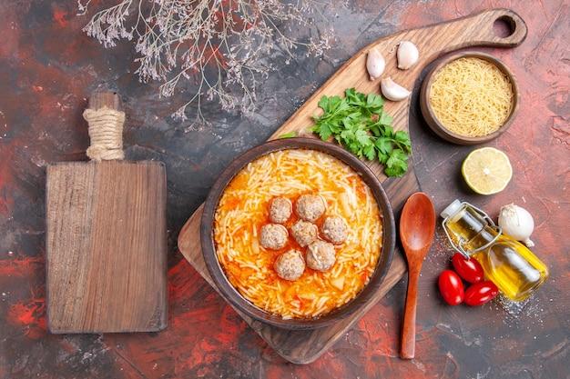 生パスタレモングリーンオイルボトルスプーンと暗いテーブルのまな板に麺が乗ったミートボールスープ