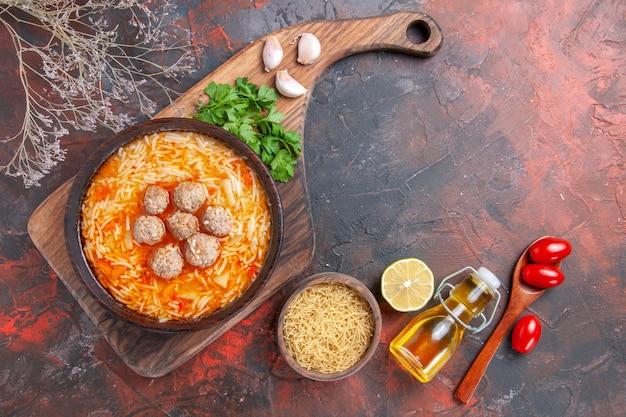 요리하지 않은 파스타에 국수를 곁들인 미트볼 수프, 어두운 배경에 레몬 그린 토마토 오일 병