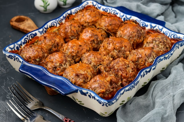 Meatballs in sour cream and tomatoes sauce in ceramic form against a dark background, horizontal orientation