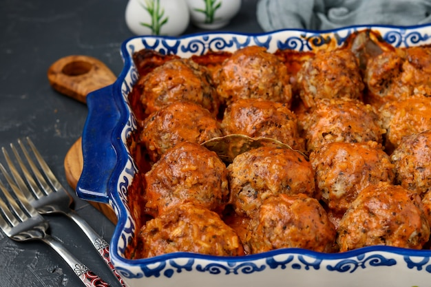 Meatballs in sour cream and tomatoes sauce in ceramic form against a dark surface, horizontal orientation