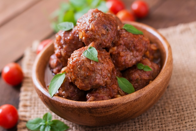 Meatballs in sweet and sour tomato sauce and basil in a wooden bowl Free Photo