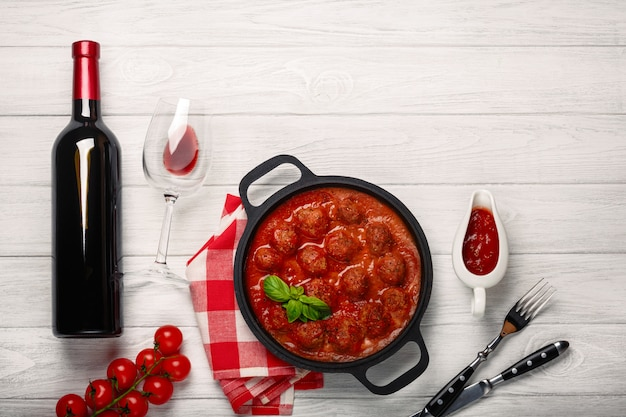 Meatballs in tomato sauce in a frying pan with bottle of wine, two glasses, knife and fork on a white wooden board