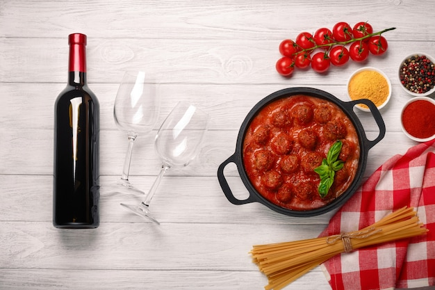 Meatballs in tomato sauce in a frying pan with cherry, tomatoes, bottle of wine and two glasses