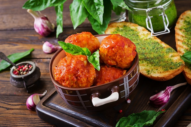 Meatballs in tomato sauce and toast with basil pesto. dinner. tasty food.