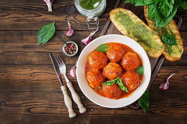 Meatballs in tomato sauce and toast with basil pesto.