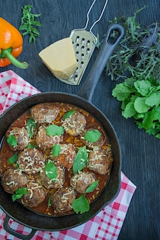 Meatballs in tomato sauce with greens.