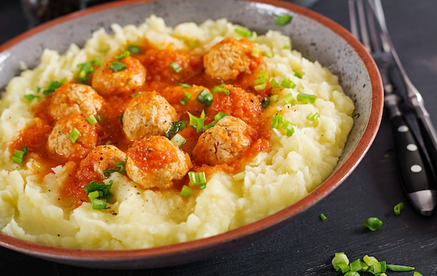 Meatballs in tomato sauce with mashed potatoes in bowl.