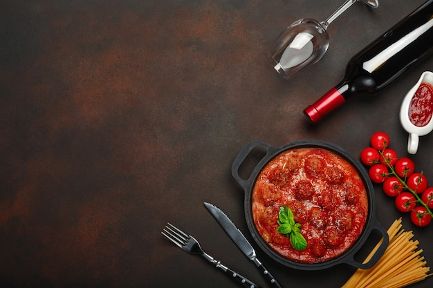 Meatballs in tomato sauce with spices, cherry tomatoes, pasta and basil in a frying pan with bottle of wine and wineglass on rusty brown background