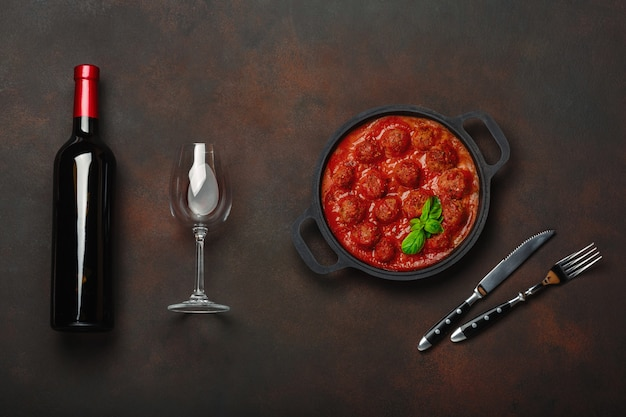 Meatballs in tomato sauce with spices, cherry tomatoes, pasta and basil in a frying pan with bottle of wine