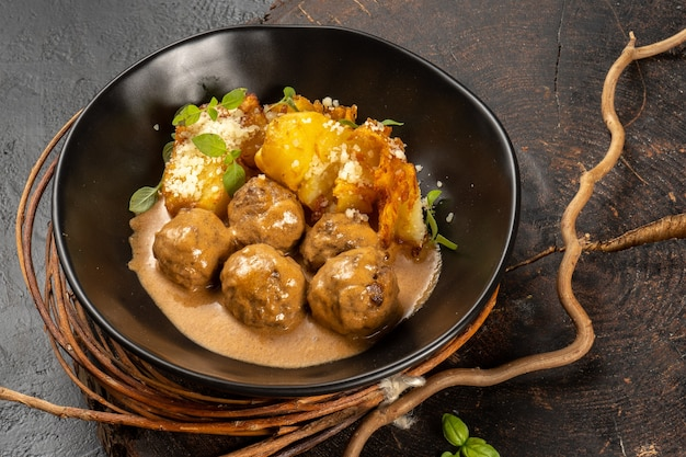 Meatballs with gravy and baked potato garnish. a hot main course in a beautiful black plate
