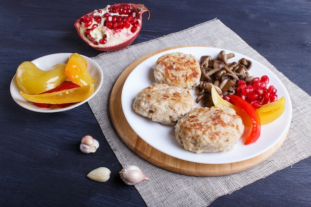 Meatballs with rice mushrooms, sweet peppers and pomegranate seeds on black wooden.