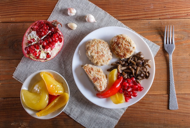 Meatballs with rice mushrooms, sweet peppers and pomegranate seeds on brown wooden.