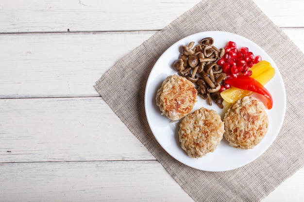 Meatballs with rice mushrooms, sweet peppers and pomegranate seeds on wooden with copyspace