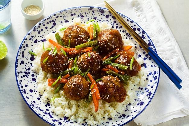 Веганские азиатские фрикадельки без мяса в кисло-сладком соусе с рисом и тушеными овощами. сбалансированный обед или полезный ужин. уличная забегаловка