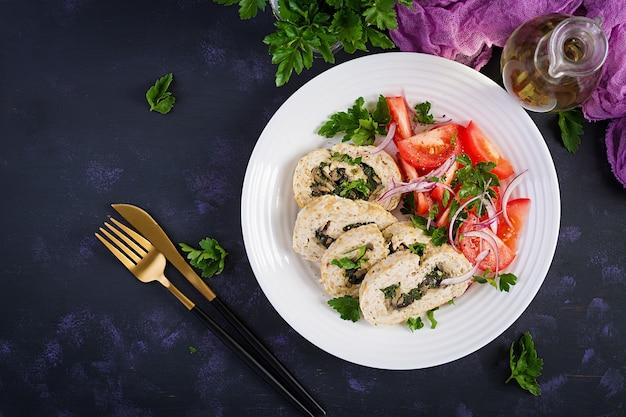 Рулет из мясного рулета, фаршированный шпинатом, оливками, грибами и салатом из помидоров. диетическое меню. вид сверху, плоская планировка