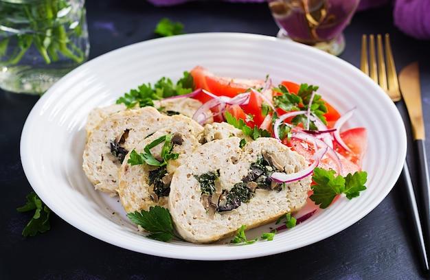 Рулет из мясного рулета, фаршированный шпинатом, оливками, грибами и салатом из помидоров. диетическое меню.
