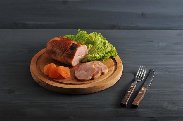 Мясной рулет с курагой и салатом на деревянной круглой доске