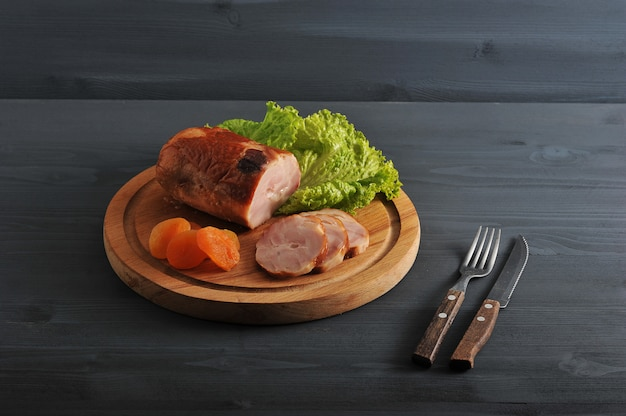 Meatloaf with dried apricots and lettuce on a wooden round board
