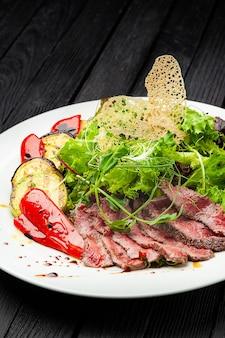Мясо, овощи на гриле и зелень в белой тарелке