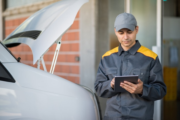 Mechainc using a tablet in front of a van